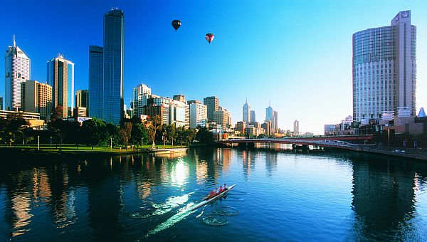 Rowers and hot air balloons over Melbourne skyline and Yarra River